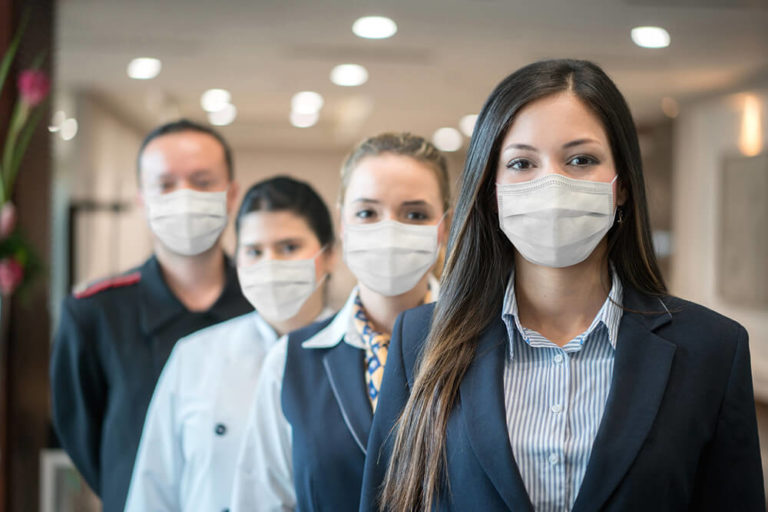 A row of hospitality employees with masks on during the pandemic